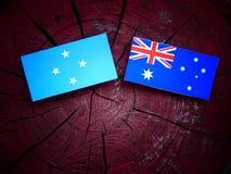 Micronesian flagga med den australiska flaggan på en isolerad trädstubbe royaltyfria bilder