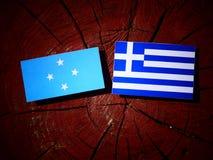 Micronesian flagga med den grekiska flaggan på en isolerad trädstubbe arkivfoto