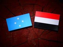 Micronesian flagga med den jemenitiska flaggan på en isolerad trädstubbe royaltyfri foto