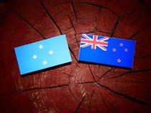 Micronesian flagga med den nyazeeländska flaggan på en isolerad trädstubbe royaltyfria foton