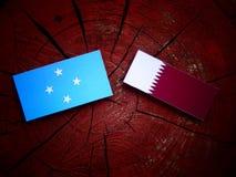 Micronesian flagga med den Qatari flaggan på en isolerad trädstubbe fotografering för bildbyråer