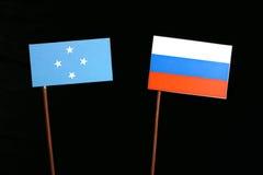 Micronesian flagga med den ryska flaggan som isoleras på svart fotografering för bildbyråer