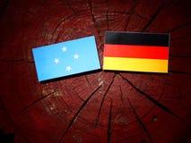 Micronesian flagga med den tyska flaggan på en trädstubbe arkivfoto