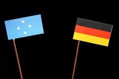 Micronesian flagga med den tyska flaggan som isoleras på svart fotografering för bildbyråer