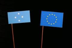 Micronesian flagga med EU-flaggan för europeisk union som isoleras på svart arkivfoton