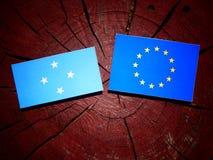 Micronesian flagga med EU-flaggan på en isolerad trädstubbe royaltyfri fotografi