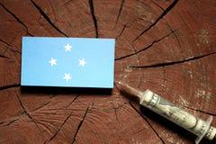 Micronesian flagga på en stubbe med injektionssprutan som injicerar pengar royaltyfria foton