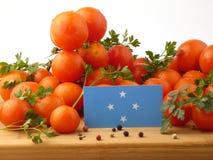 Micronesian flagga på en träpanel med tomater som isoleras på en w arkivbilder