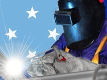 MICRONESIAN WELDER MED BAKGRUND AV HANS FLAGGA royaltyfri foto