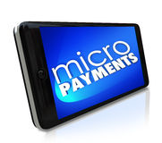 Micropayments Sending Money Via Smart Cell Phone Mobile Paying. Micropayments word on a smart cell phone to illustrate buying goods or merchandise from a website Royalty Free Stock Photos