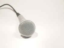 Microphone. Silver microphone with black cord on white background Royalty Free Stock Photos