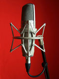 Microphone. In front red background Royalty Free Stock Photography