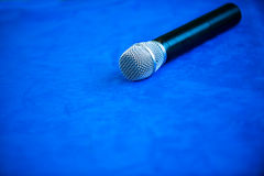 Microphone. Simple microphone on table, blue tone stock image