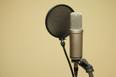 Microphone. On stand with yellow background Royalty Free Stock Photography