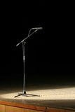 Microphone. On wooden stage, black background Royalty Free Stock Images