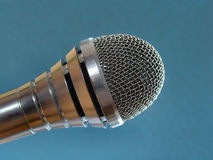 Microphone. A silver microphone on blue background royalty free stock photos