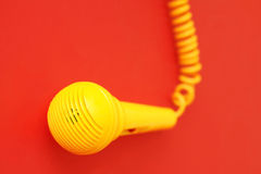 Microphone. A yellow microphone on red Royalty Free Stock Image