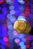 Microphone. A microphone alone on stage full of out of focus color lights Stock Images