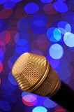 Microphone. A microphone alone on stage full of out of focus color lights Royalty Free Stock Image