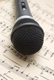 Microphone. And music notes on the table Stock Photo