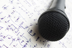 Microphone. And music notes on the table Stock Photos