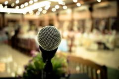 Microphone on abstract blurred of front podium and speech in seminar room or speaking conference hall light, Event meeting. Bokeh background stock images