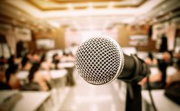 Microphone on abstract blurred of front podium and speech in seminar room or speaking conference hall light, Event meeting. Bokeh background, black and white stock photography