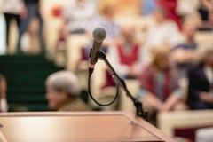 Microphone on abstract blurred of speech in seminar room or speaking conference hall light, Event Background royalty free stock photos