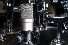 Microphone Against Diffused Studio Background. Microphone against diffused drum kit in a recording studio Stock Image