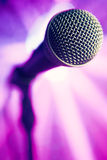 Microphone against purple background Royalty Free Stock Image