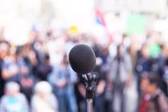 Microphone au foyer, contre la foule brouillée Photographie stock libre de droits