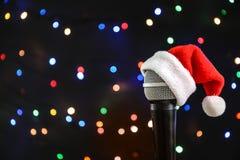 Microphone avec le chapeau de Santa contre les lumières brouillées images libres de droits
