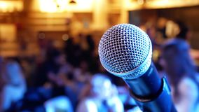 Microphone on the background of the hall with people. With blurred bokeh stock video