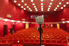Microphone on a background of red hall with seating for spectators. Chairs for the audience stock image