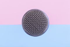 Microphone background. Top view of the microphone on a pink blue background, singing accessory royalty free stock images
