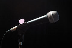 Microphone on the bar. Top down illuminated music microphone on the bar with a pick and cable - still life Stock Photos