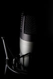 Microphone on black background. A microphone sits in front of a black background Royalty Free Stock Images