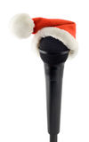 Microphone black in santa claus hat Stock Images