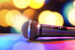 Microphone on black table and colored lights background Royalty Free Stock Photos
