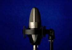 Microphone on blue background. Proffessional record studio microphone on abstract dark blue background Stock Photos