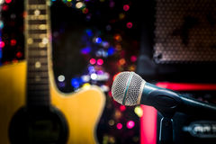 Microphone, blur guitar background. Guitar Instrument Microphone Audio festive lights Stock Photography