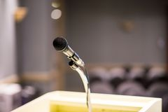 Microphone on blurred in seminar room or conference hall background. Close up Stock Photography