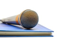 Microphone on a book against white background. For speaking, learning and teaching concept stock photos