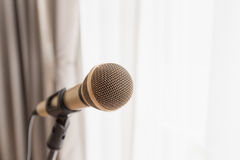 Microphone with bright light from window. Close focus on classic gold wired microphone on stand with bright light from window Royalty Free Stock Photography