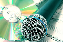 Microphone with CD. Microphone and CD in close-up frame with the notes in background Royalty Free Stock Photography