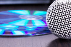 Microphone and cd disks on black table Royalty Free Stock Image
