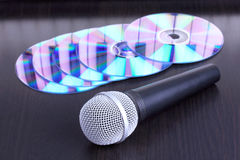 Microphone and cd disks on black table Stock Image