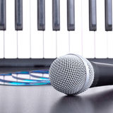 Microphone, cd disks and piano keyboard on black table Stock Image