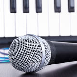 Microphone, cd disks and piano keyboard on black table Royalty Free Stock Photography
