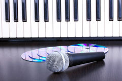 Microphone, cd and piano keyboard on black table Royalty Free Stock Image